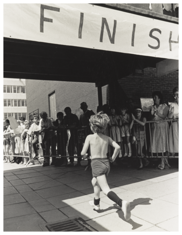 Young boy crossing finish line, Wester Hailes fun run