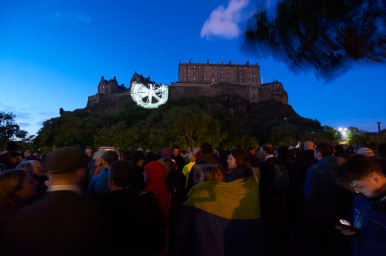 Crowds awaiting the start of the opening event of the Edinburgh International Festival, 'Deep Time', on Castle Terrace