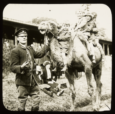 A zookeeper leads a group of four children on a camel ride.
