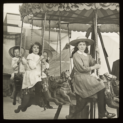 Image of children in their Sunday best clothes and hats sitting on carousel horses.