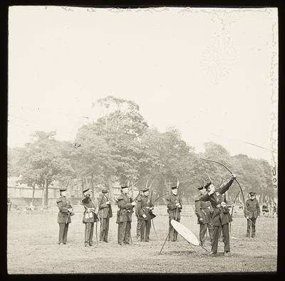 A group of uniformed archers practice archery in a park.