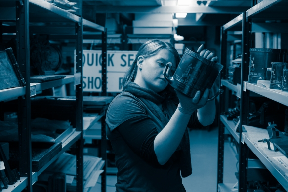 A curator examining an archival object in a museums collections store room.
