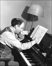 Composer Dimitri Tiomkin sat at a piano