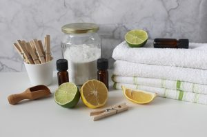 Selection of objects including towels, citrus fruit, essential oils and wooden pegs