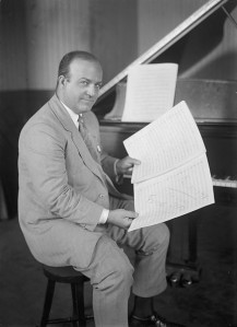 Portrait of composer Ferde Grofe sat at a piano.